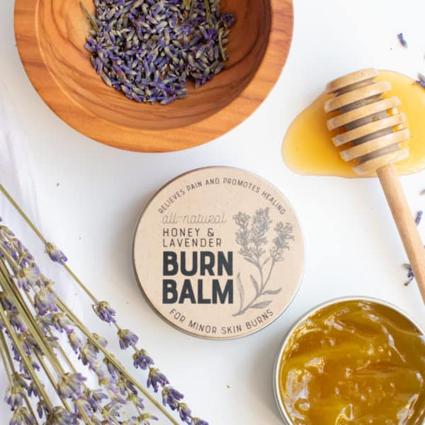 An open tin of burn balm sits in front of a lidded and labeled tin. A honey dipper, bowl of lavender buds, and sprigs of lavender are nearby.