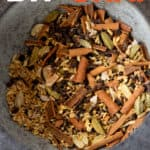 """Crushed spices fill a gray mortar, after being crushed with a pestle. A text overlay reads """"DIY Chai. Loose Leaf or Bags!"""""""