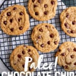 """Six almond flour chocolate chip cookies sit on a round wire rack to cool. A text overlay reads """"Paleo! Chocolate Chip Cookies."""""""