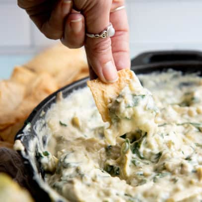 A hand dips a pita chip into a skillet of vegan spinach artichoke dip.