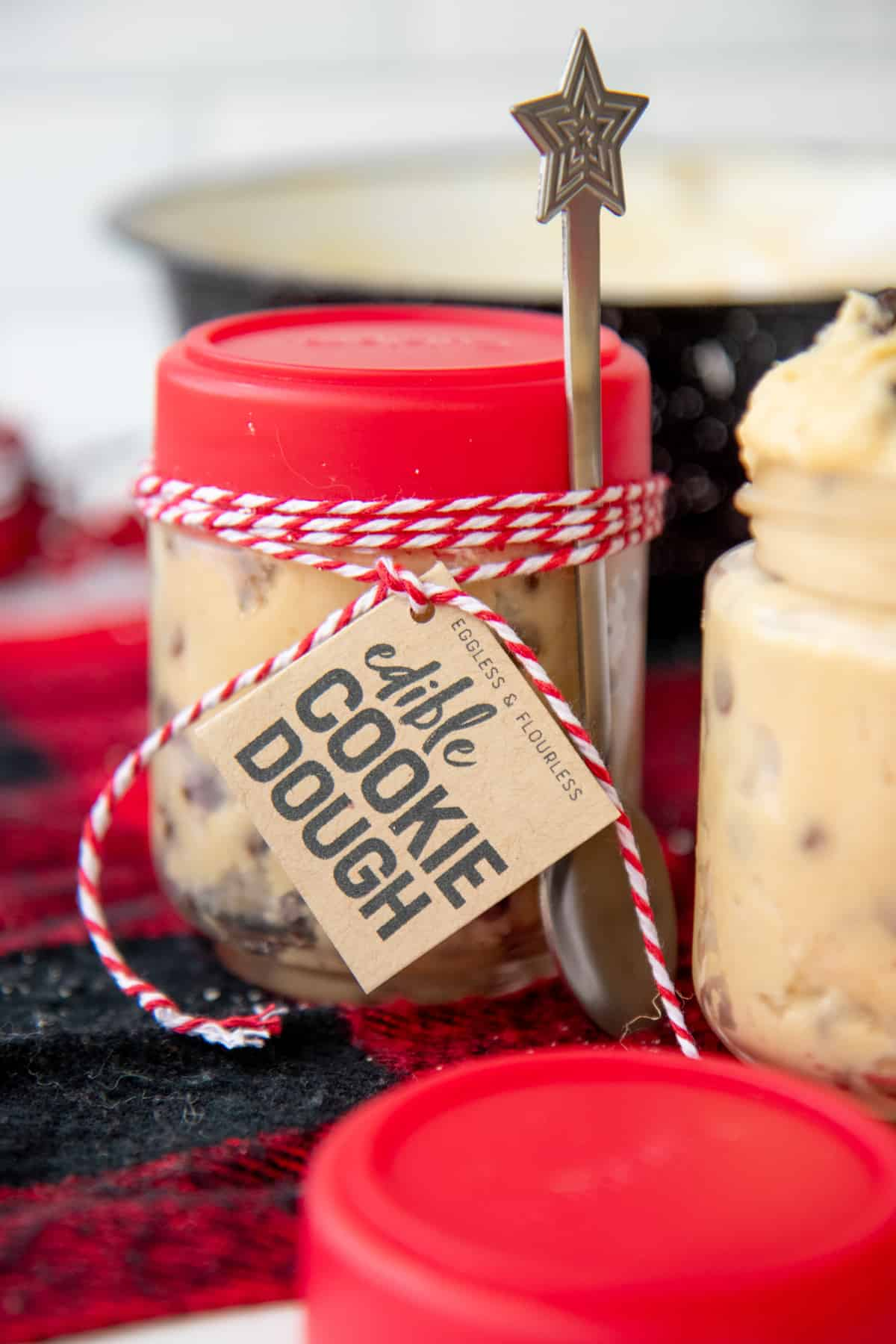 "A small jar with a red lid and ""Edible Cookie Dough"" label is filled with chocolate chip cookie dough. A silver holiday-themed spoon is tied to the jar with red and white baker's twine."