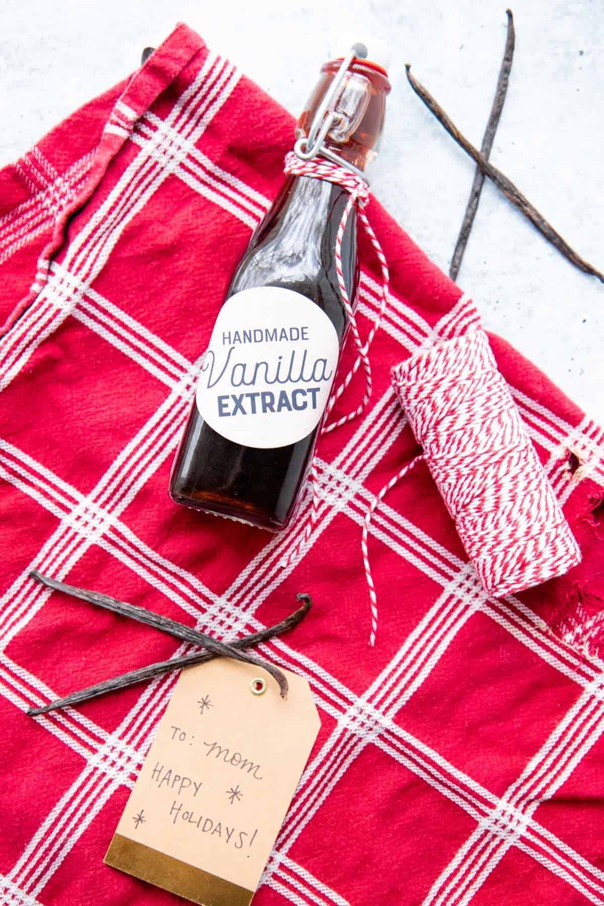 A bottle of homemade vanilla extract lays on red and white fabric, surrounded by whole vanilla beans.