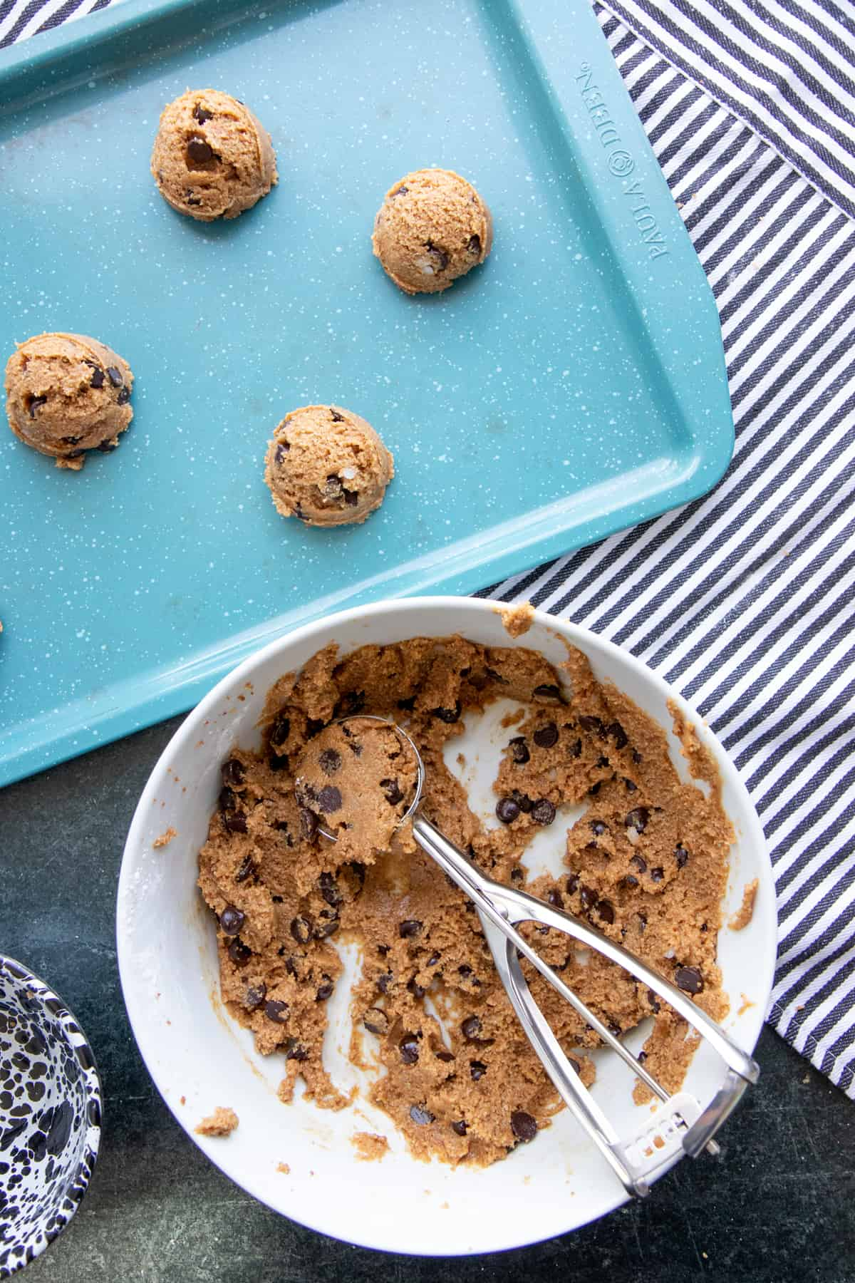 A cookie scoop sits in a bowl of paleo chocolate chip cookie dough. The bowl is next to a turquoise baking sheet that already has some balls of dough sitting on it.