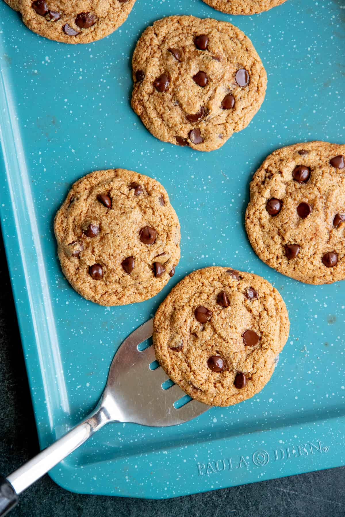 A spatula slides under a paleo chocolate chip cookie to remove it from a turquoise baking sheet.