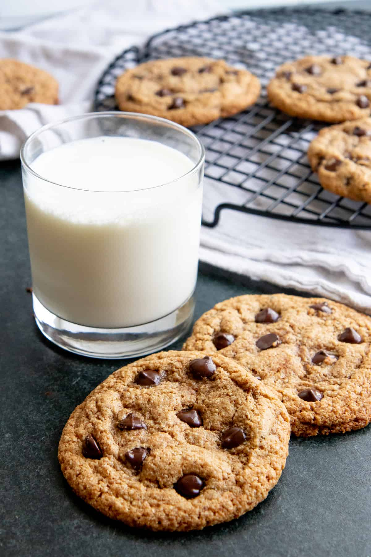 Two paleo chocolate cookies sit next to a glass of almond milk. A wire rack with more cookies is in the background.