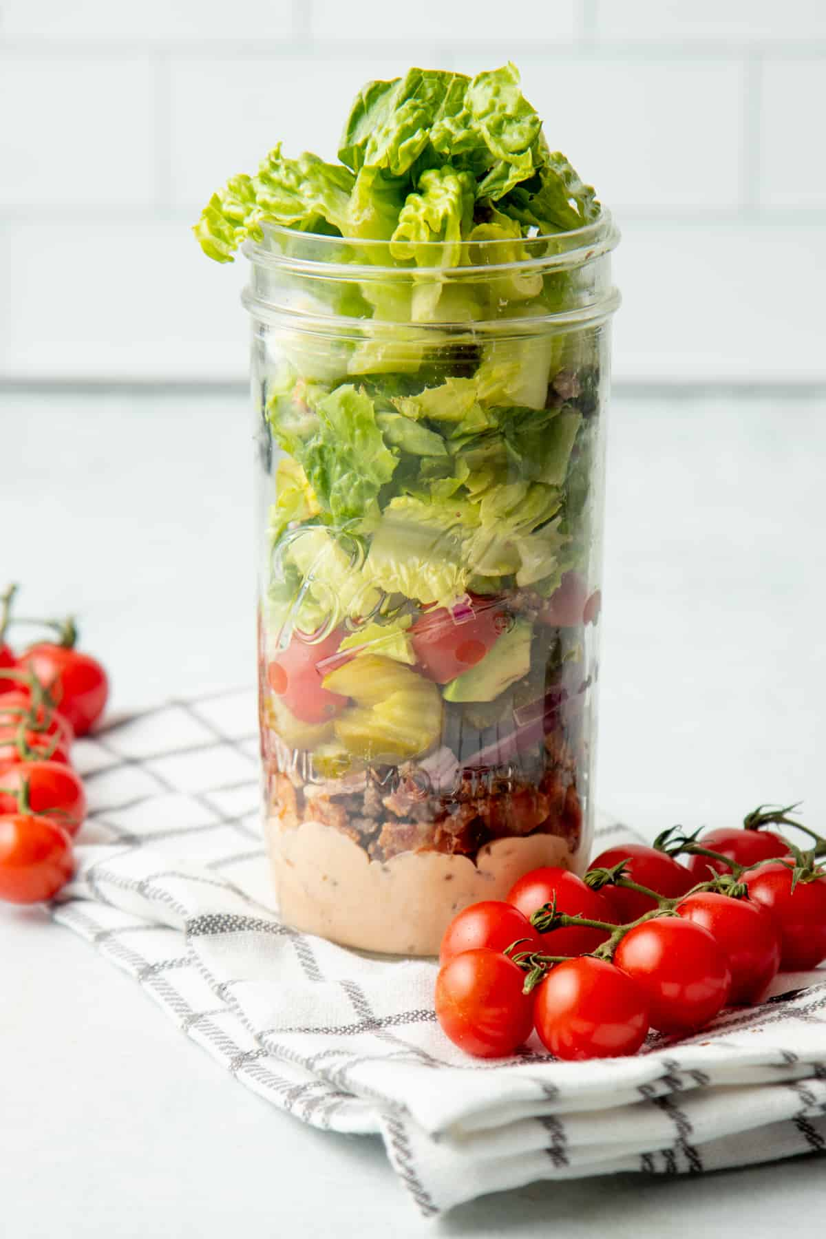 Ingredients for a burger bowl salad are layered in a wide-mouth mason jar