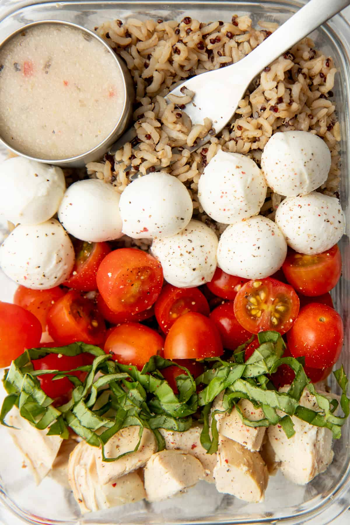 A glass dish is arranged with ingredients for a caprese grain bowl. A cup of dressing rests in the upper left corner.
