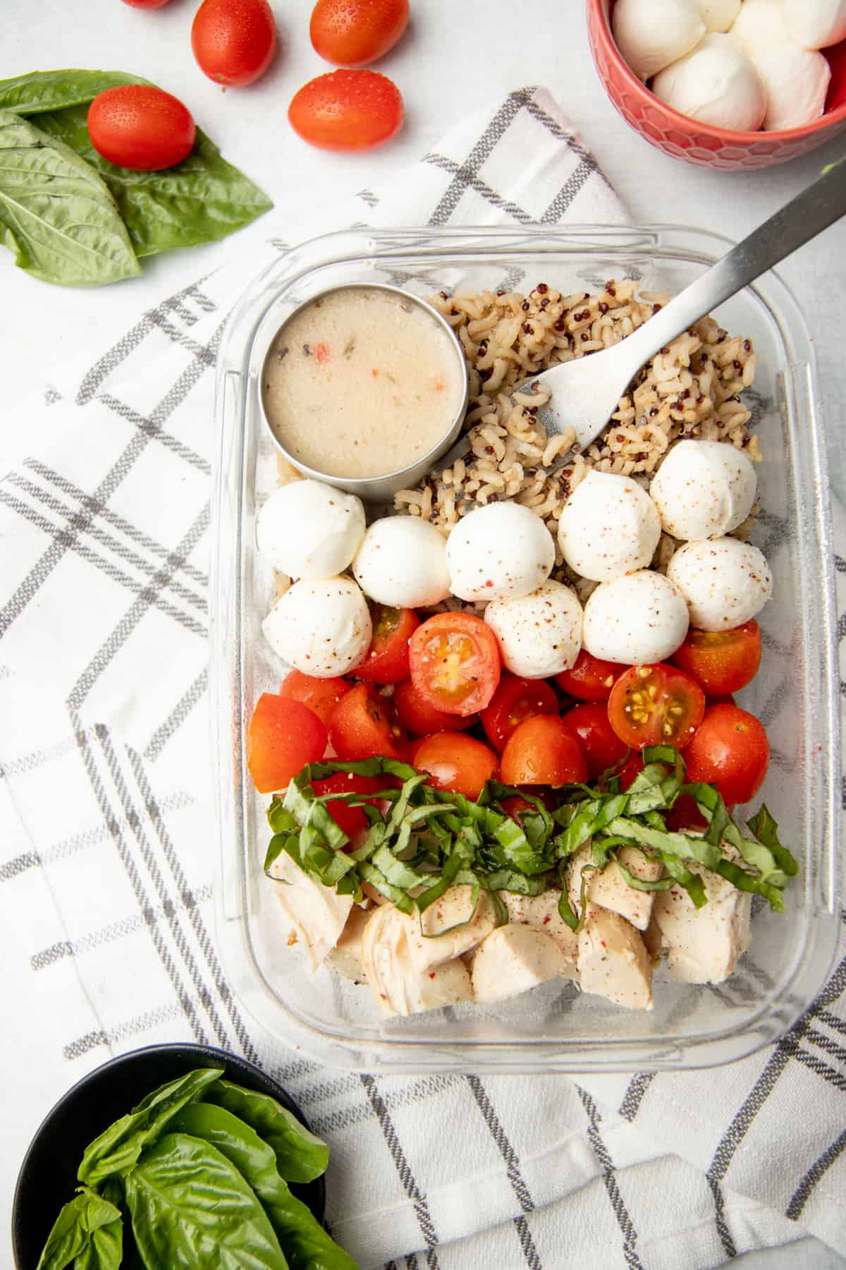 A glass dish is arranged with ingredients for a caprese chicken quinoa bowl. A cup of dressing rests in the upper left corner.