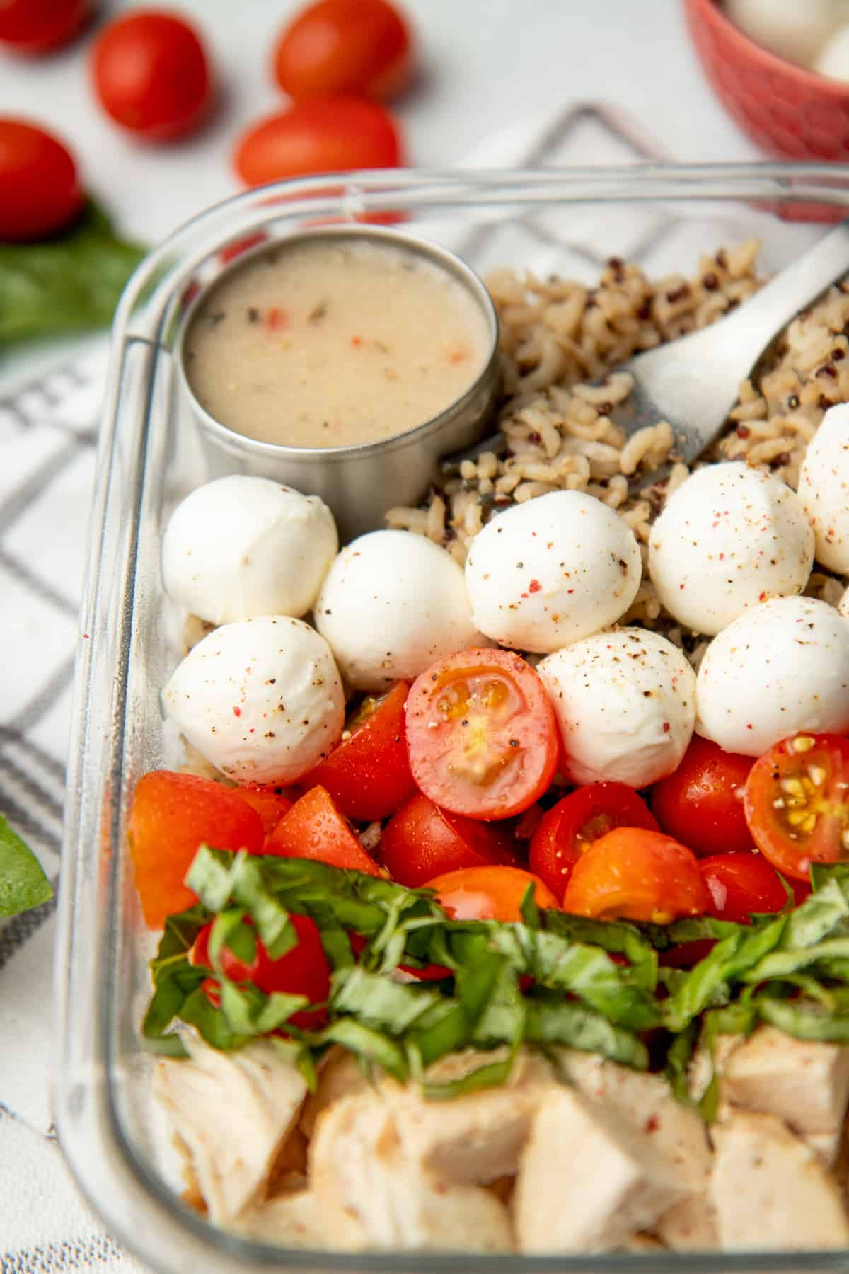 A glass dish is arranged with ingredients for caprese grain bowl. A cup of dressing rests in the upper left corner.