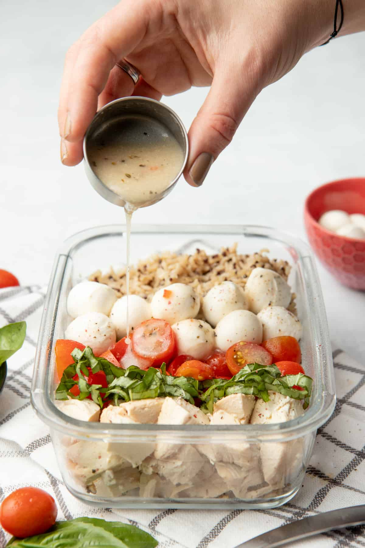 A hand pours dressing over a glass container of chicken, basil, tomatoes, cheese, and grains.