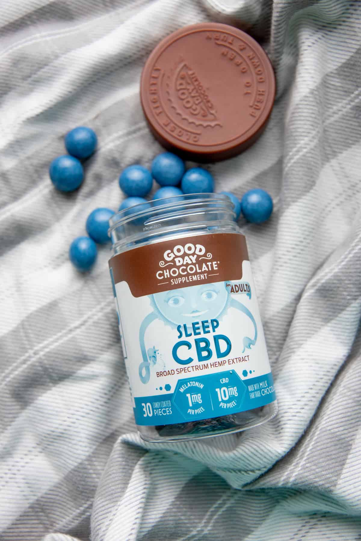 """A bottle of Good Day Chocolates """"Sleep CBD"""" spills out onto a white piece of fabric."""