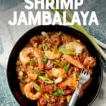 "A piece of sausage rests on a fork inside a bowl of jambalaya. Whole green onions lay alongside the bowl. A text overlay reads ""Instant Pot Shrimp Jambalaya. With Paleo and Whole30 Options."""