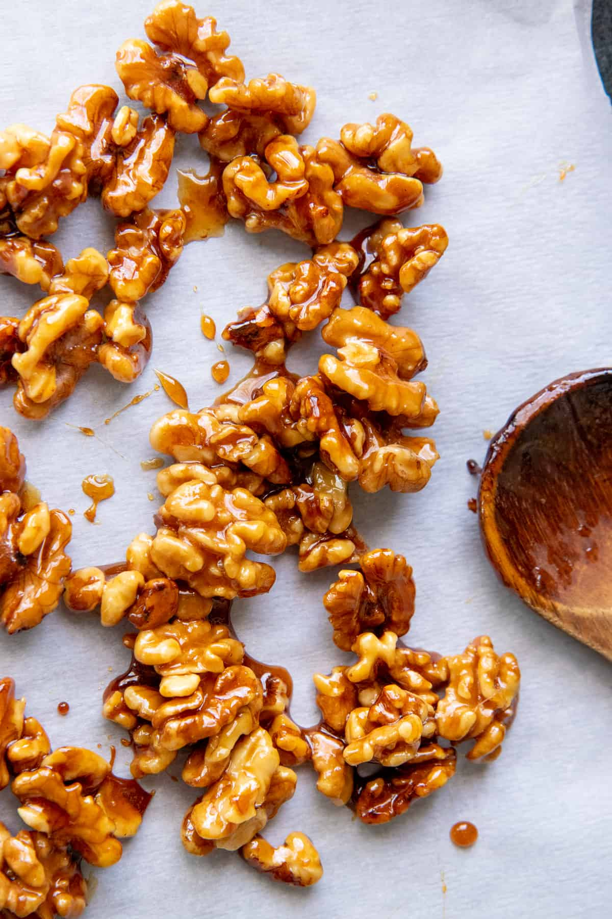 Maple candied walnuts are spread out on a piece of parchment paper.