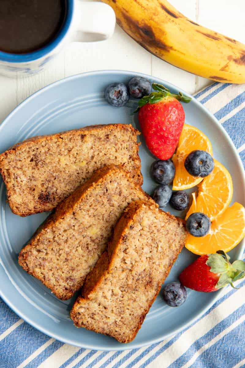 Three slices of almond flour banana bread on a blue plate with mixed fruit, next to a cup of coffee.
