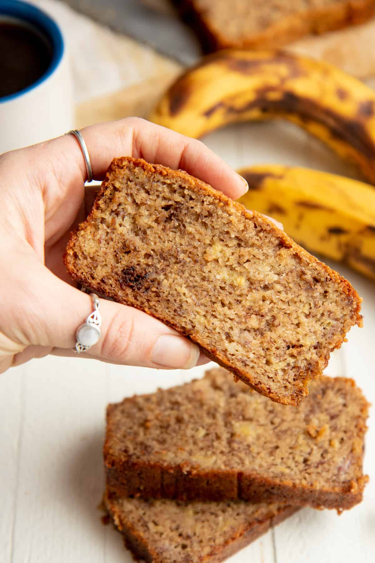 A woman's hand holds a slice of paleo banana bread over a stack of other slices.