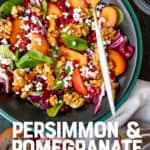 """A fork rests on a dark bowl, filled with persimmon and pomegranate salad. A text overlay reads """"Persimmon & Pomegranate Spinach Salad."""""""