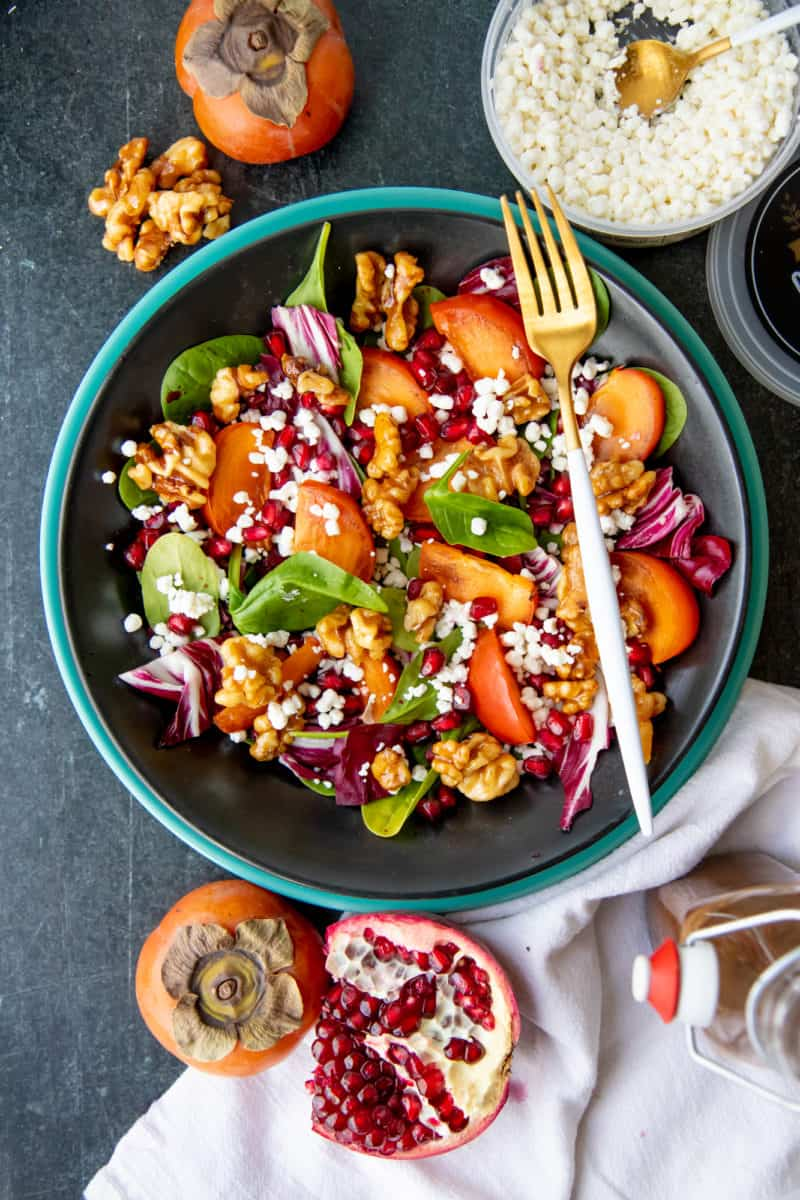 A fork rests on a dark bowl, filled with persimmon and pomegranate salad.