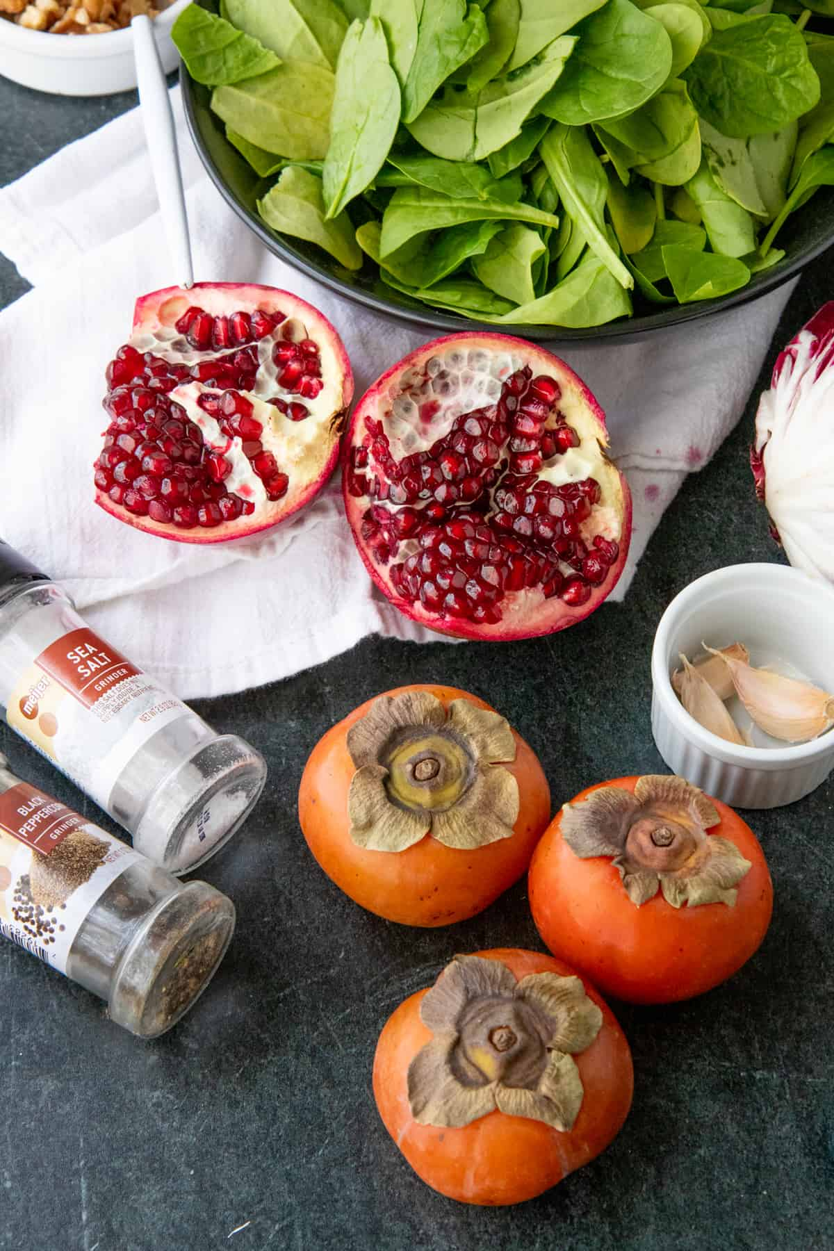 Persimmons, pomegranates, and spinach sit next to salt, pepper, and garlic.
