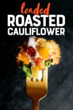 "A gold fork holds a bite of loaded roasted cauliflower in front of a dark background. A text overlay reads ""Loaded Roasted Cauliflower."""