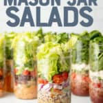 """Tall mason jars sit on a white surface in front of a white wall. The jars are layered with salad ingredients. The jar in the front includes dressing, black beans, onions, tomatoes, and lettuce. Text overlay reads, """"The Ultimate Guide to Mason Jar Salads."""""""