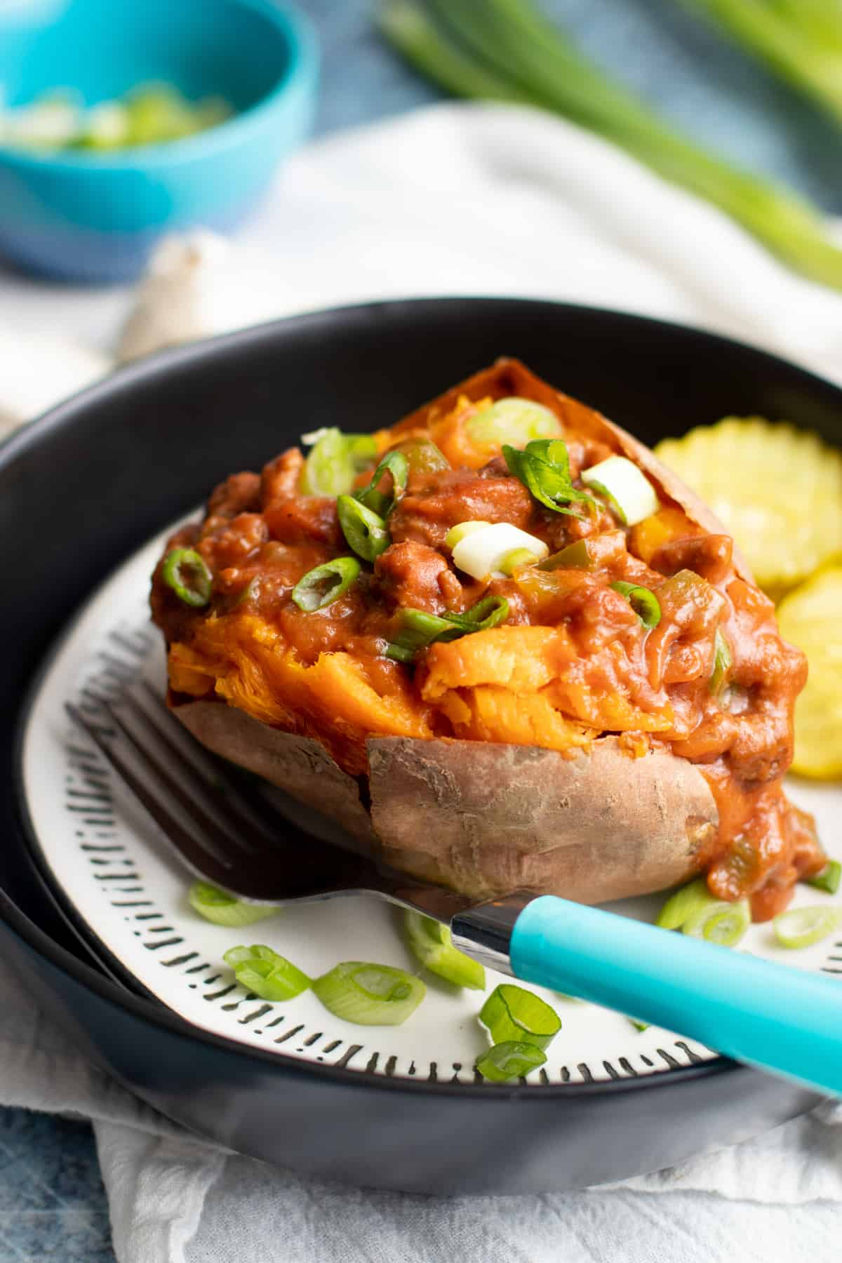 Sweet potato stuffed with a beef sauce on a plate, with a teal-handled fork resting on the side of the plate.