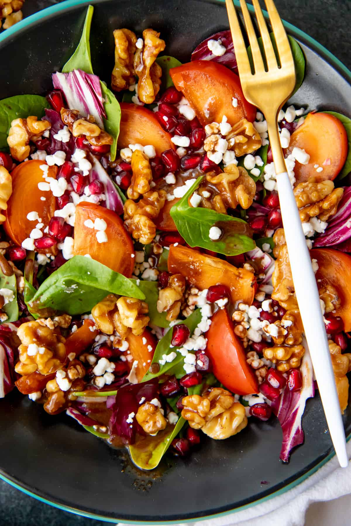 Close up of a salad filled with pomegranates, persimmons, spinach, candied walnuts, and goat cheese.
