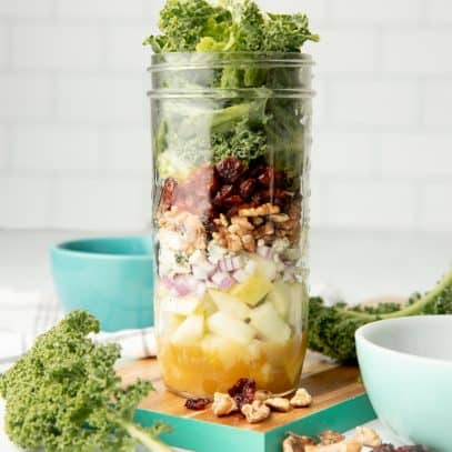 An apple walnut mason jar salad sits on a teal-edged cutting board, surrounded by kale and walnuts.