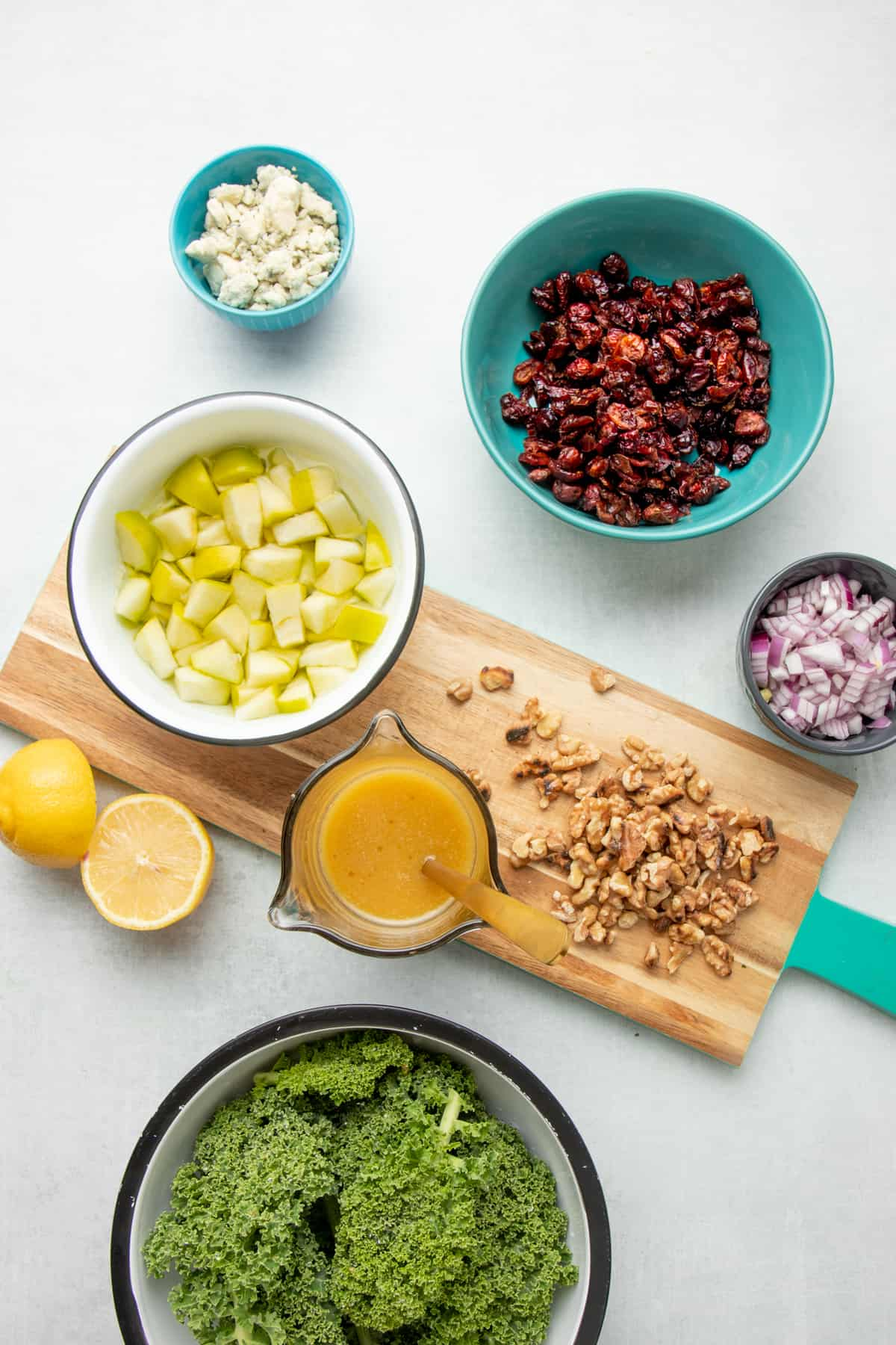 Ingredients for an apple walnut salad are arranged in individual teal and white bowls.