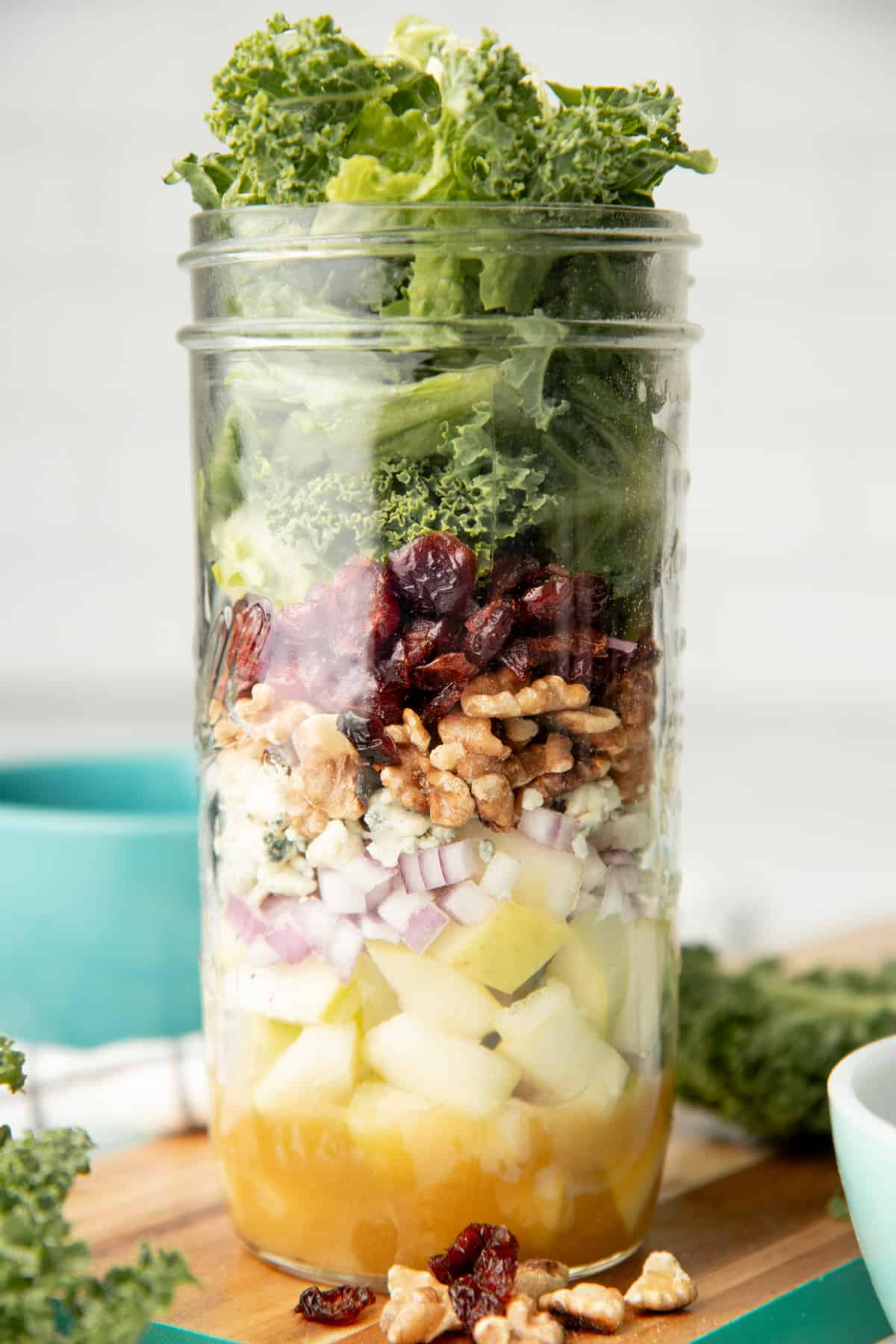 Ingredients for apple walnut salad are layered in a mason jar.