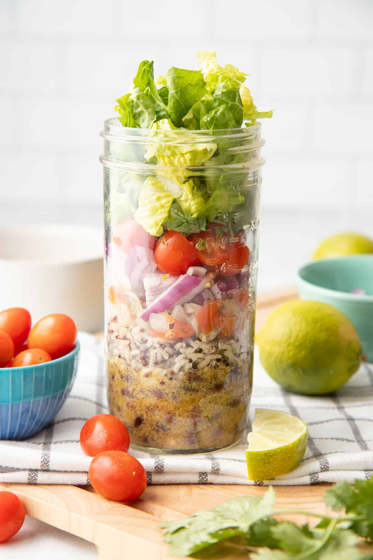 A glass jar layered with dressing, rice, beans, pico de gallo, onions, tomatoes, cilantro, and lettuce sits on a folded dish towel. Extra ingredients are scattered around the jar.