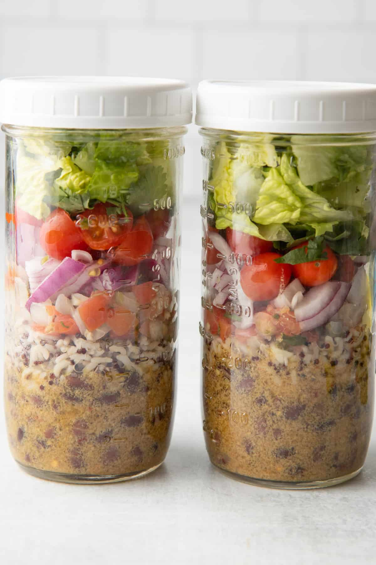 Two tall mason jars sit on a white countertop. The jars are layered with ingredients for black bean fiesta salad. Jars are topped with a white lid.