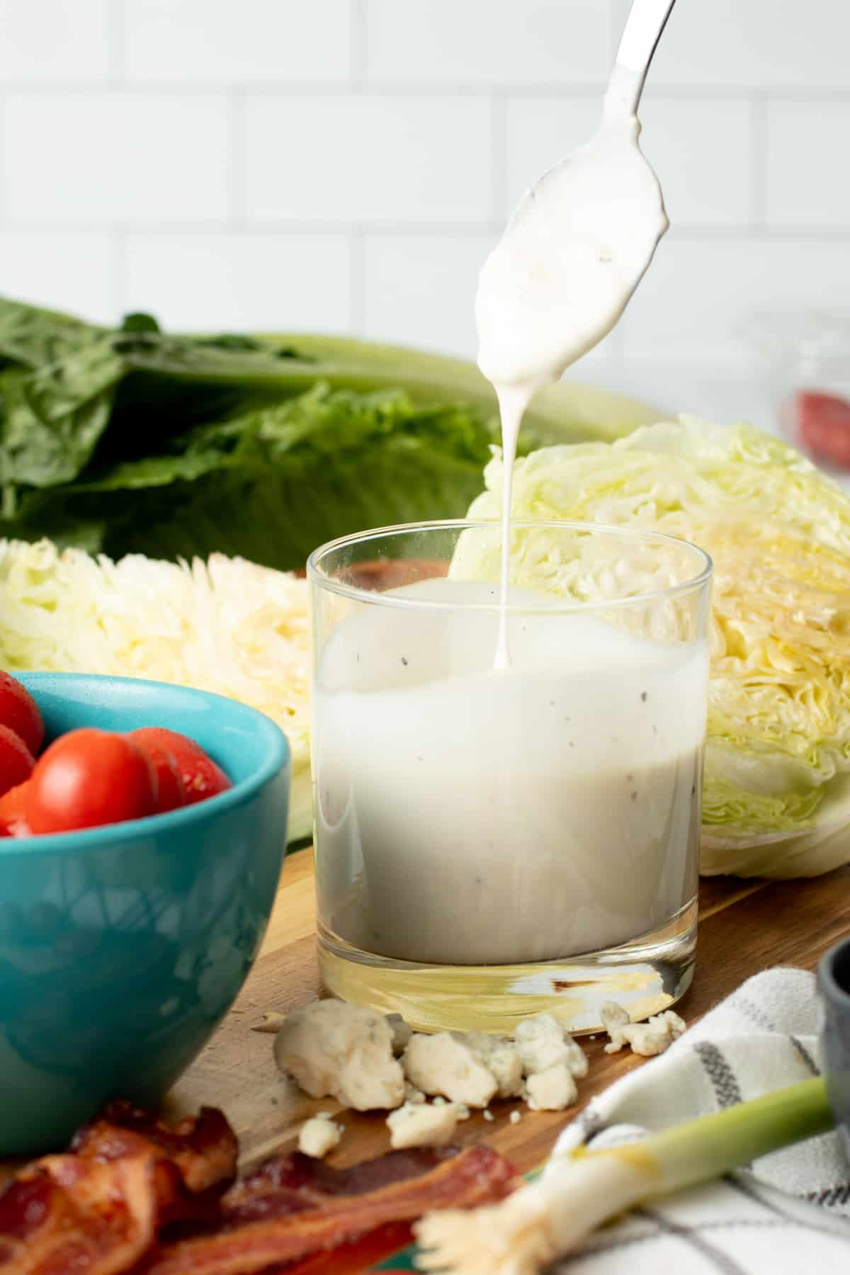 A spoon drizzles blue cheese dressing into a glass of dressing.