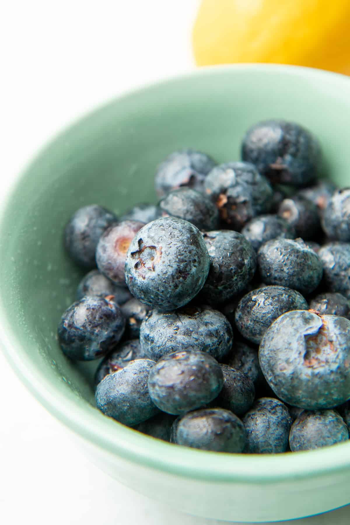 Blueberries sit in a teal bowl.