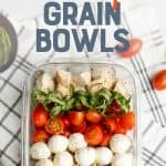 """A glass dish filled with grain bowl ingredients sits on a brown and white dishtowel. Tomatoes and mozzarella sit on the side. A text overlay reads """"Meal Prep Chicken Caprese Grain Bowls."""""""