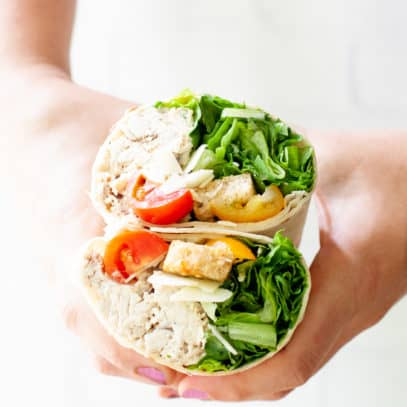 Two hands hold a chicken Caesar wrap that has been cut in half.