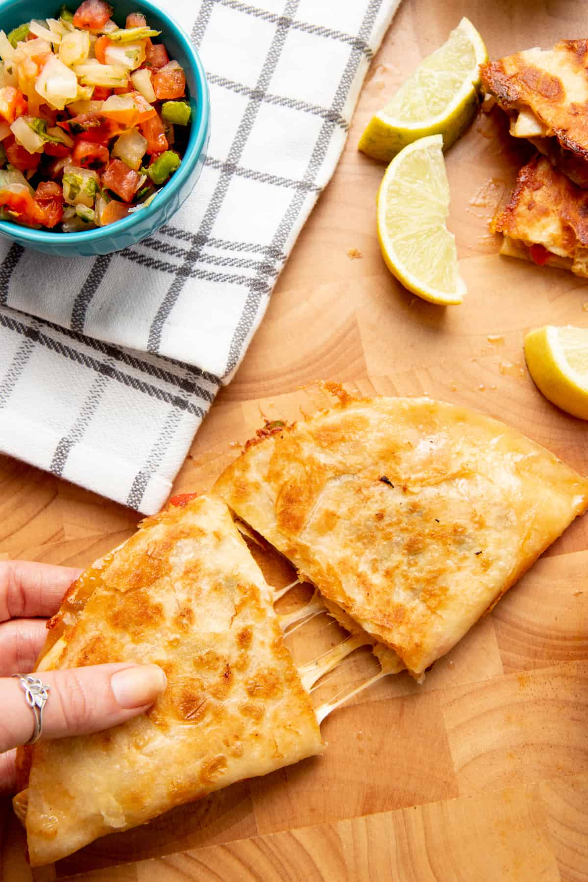 A hand pulls apart two halves of a quesadilla. A teal bowl of salsa sits on a white and brown plaid dishtowel.