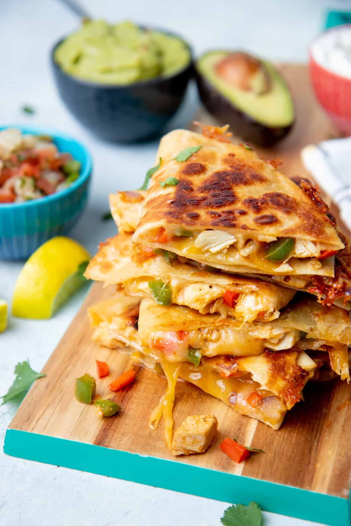 Chicken quesadillas rest on a wooden cutting board. A bowl of salsa and a bowl of guacamole sit behind them.
