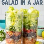 """Two mason jars are layered with chicken, black beans, tomatoes, and lettuce. A fork with a teal handle rests in front of the jars. A text overlay reads """"Chicken Taco Salad in a Jar."""""""
