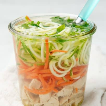 A small jar is filled with chicken zoodle soup. A spoon with a teal handle sits in the jar.