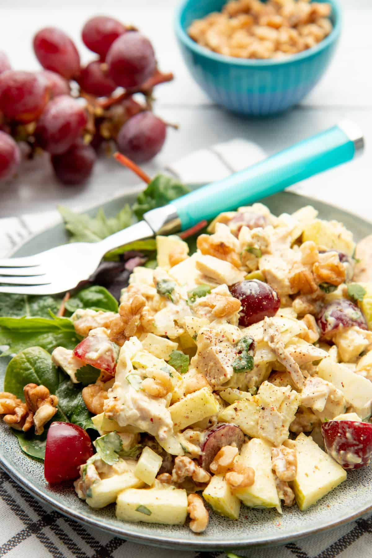 A gray plate holds chicken salad and lettuces. A blue fork rests on the plate. Grapes and walnuts are also on the table.