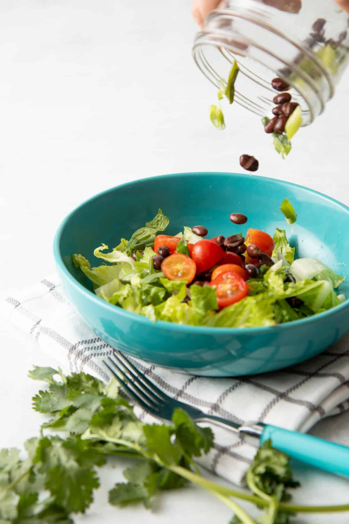 A hand pours a salad from a jar into a teal bowl. The bowl sits on a white and brown plaid dishtowel. A fork with a teal handle sits to the side of the bowl.
