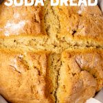 "A round loaf of Irish soda bread rests in a cast iron skillet. Text overlay reads, ""easy Irish soda bread."""