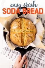"""A round loaf of Irish soda bread rests in a cast iron skillet. A hand holds the handle of the pan. Text overlay reads, """"easy Irish soda bread."""""""