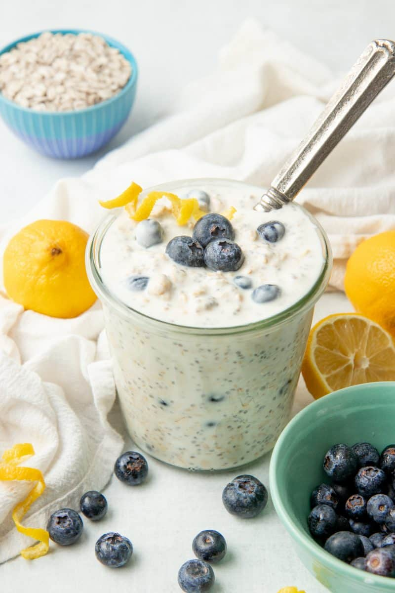 A spoon rests in a glass jar of blueberry overnight oatmeal.