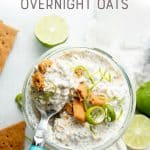 "A spoon with a blue handle sits in a jar of key lime pie overnight oats. A text overlay reads, ""Key Lime Pie Overnight Oats."""