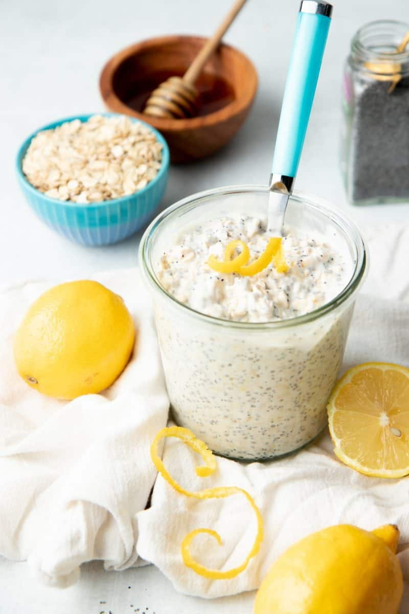 A jar is filled with lemon poppyseed overnight oats. It is topped with a twirl of lemon zest.