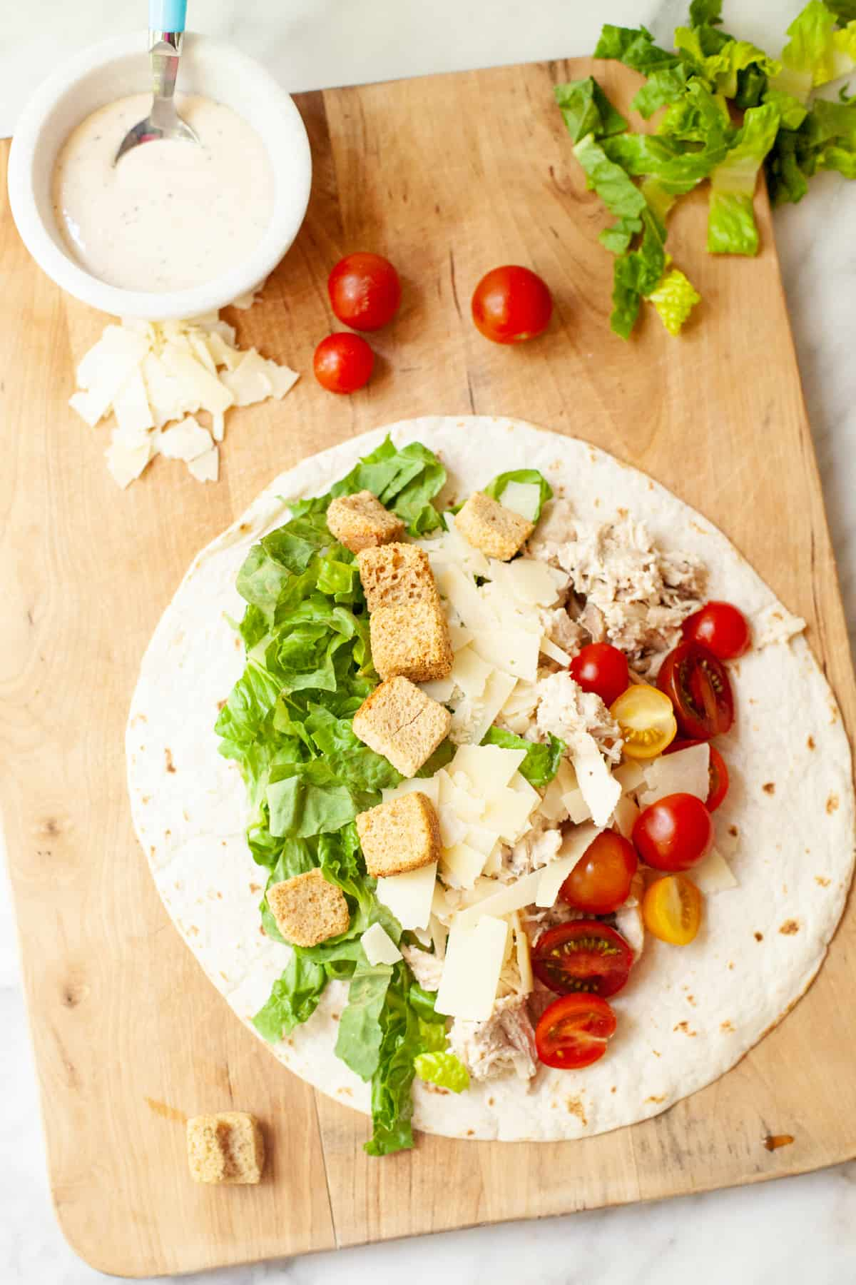 Lettuce, croutons, cheese, chicken, and tomatoes are placed on a tortilla. Dressing and tomatoes also rest on wooden cutting board.
