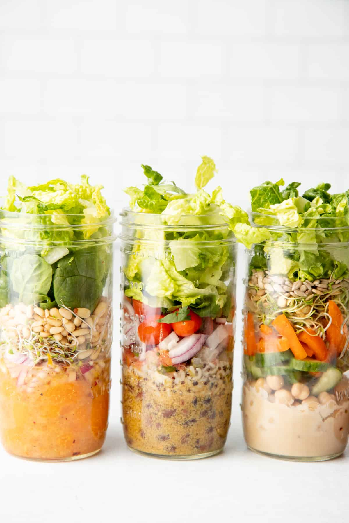 Three tall mason jars sit side-by-side in front of a white wall. Jars are layered with salad ingredients.