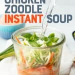 """A kettle pours water into a small jar filled with chicken, vegetables, and herbs. The jar sits on a white dishtowel. A text overlay reads """"Meal Prep! Chicken Zoodle Instant Soup."""""""