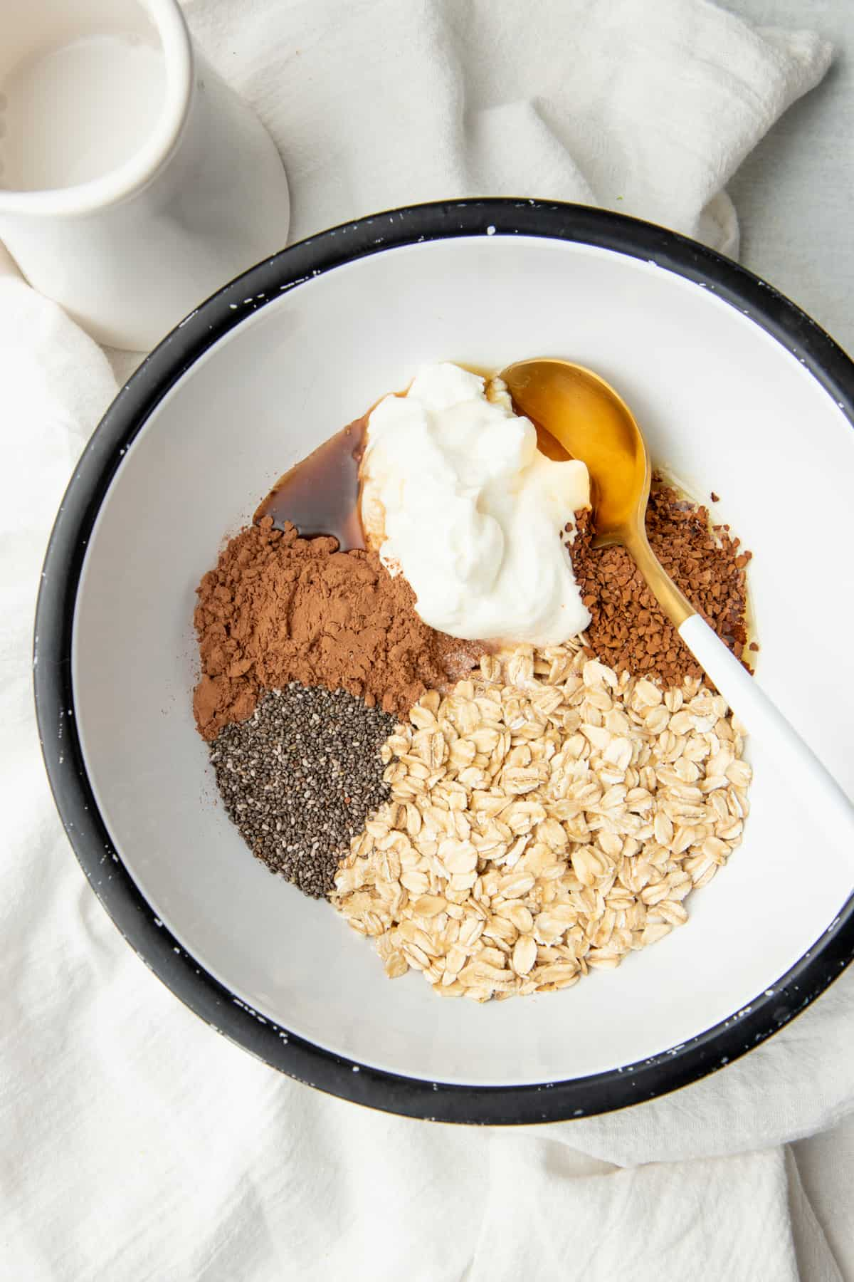 A golden spoon rests in a white bowl. Ingredients for mocha overnight oats are arranged in the bowl.